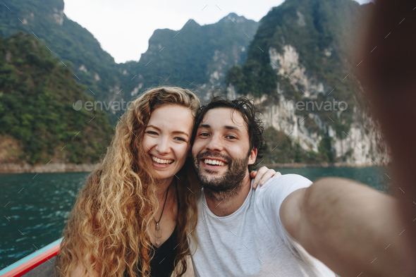 Couple taking selfie on a longtail boat - Stock Photo - Images