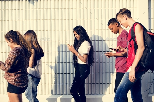 Group of young teenager friends walking home after school using smartphones addiction concept - Stock Photo - Images