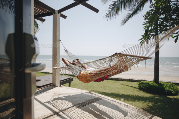Couple relaxing in a hammock by the beach - Stock Photo - Images
