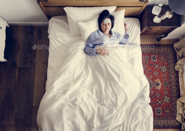 Sick Asian woman with fever sleeping on the bed - Stock Photo - Images