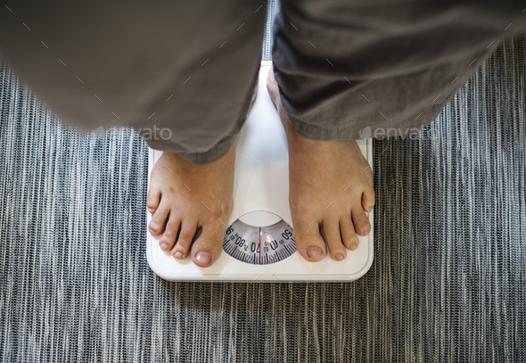 Woman standing on a scale - Stock Photo - Images