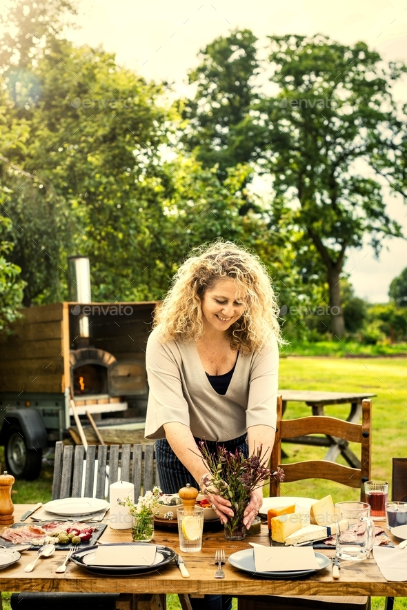 Woman preparing dinner table - Stock Photo - Images