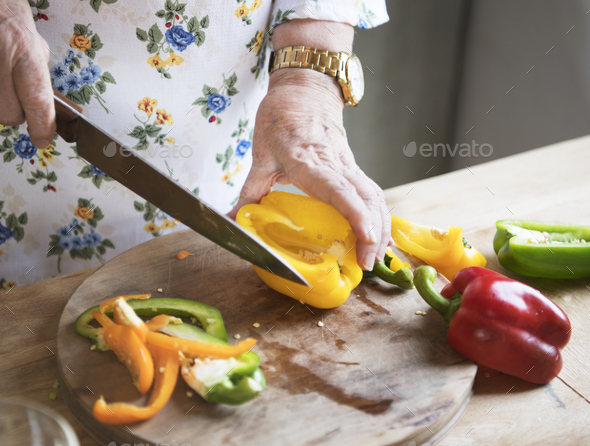 Elderly woman slicing bell peppers - Stock Photo - Images