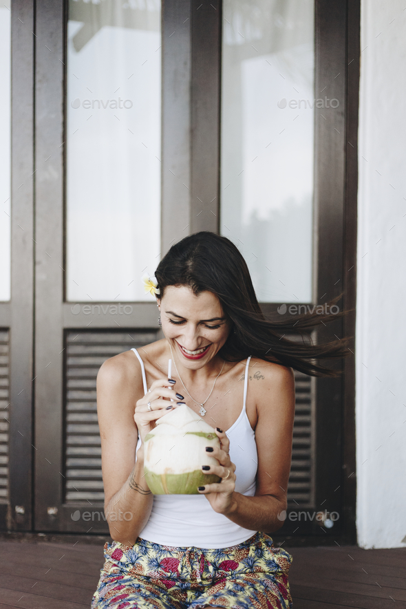 Woman drinking a fresh coconut - Stock Photo - Images