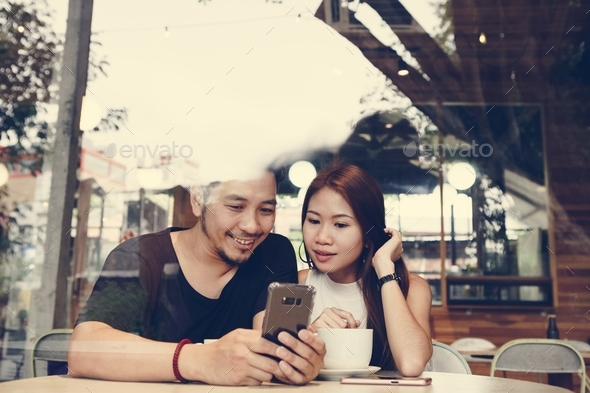 Couple using a phone at a cafe - Stock Photo - Images
