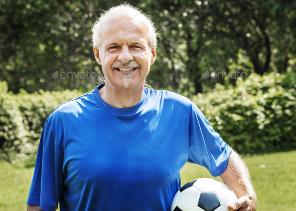 Mature man holding a football - Stock Photo - Images
