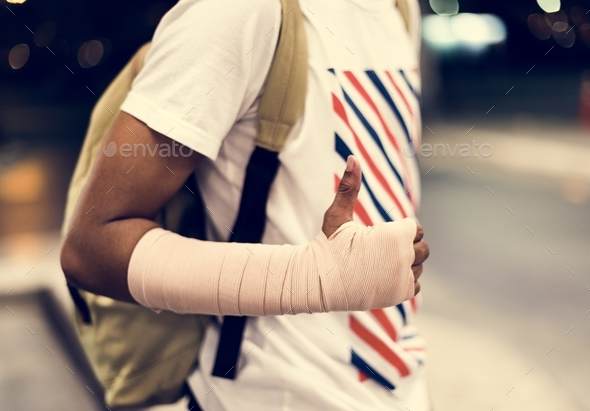Injured young man with arm support - Stock Photo - Images