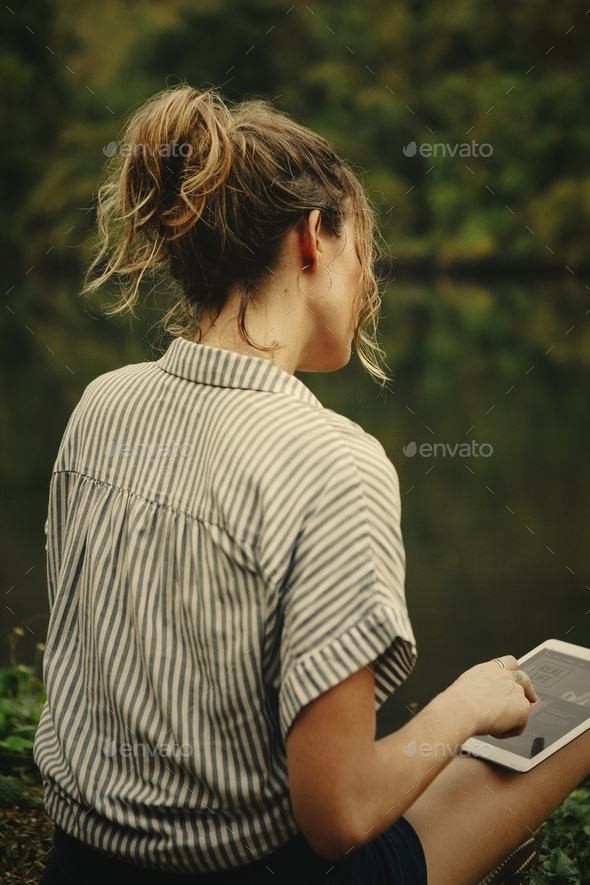 Woman alone in nature using a digital tablet with entertainment - Stock Photo - Images