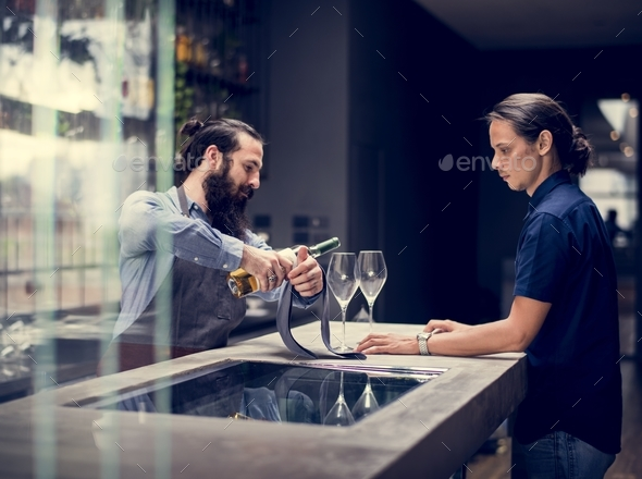 Bartender pouring a wine to the glass - Stock Photo - Images