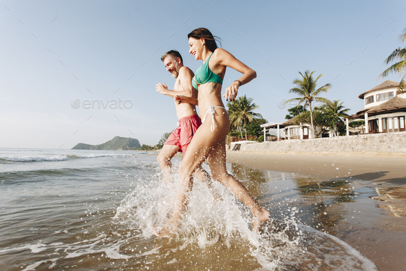 Happy couple running into the water - Stock Photo - Images