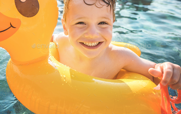 Happy boy and a yellow duck tube in the pool - Stock Photo - Images