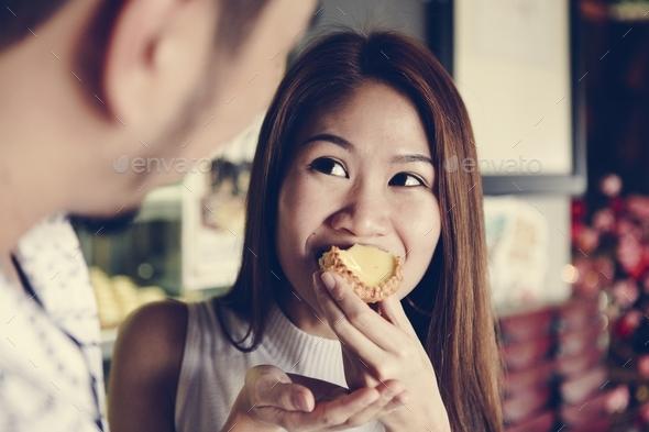 Asian girl having a bite of tart - Stock Photo - Images