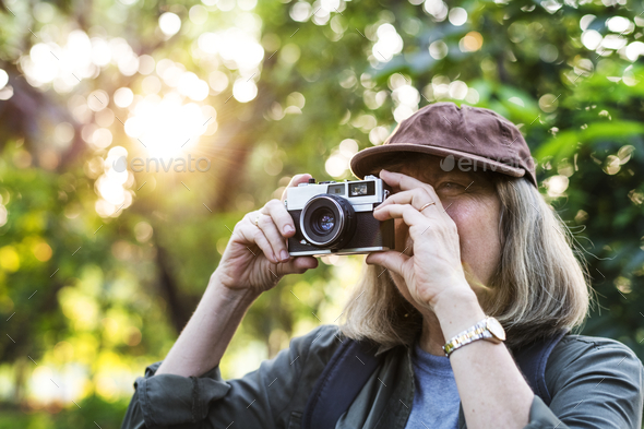 Senior trekker taking a photo with a film camera - Stock Photo - Images