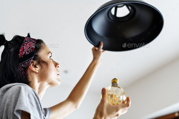 Woman changing lightbulb - Stock Photo - Images