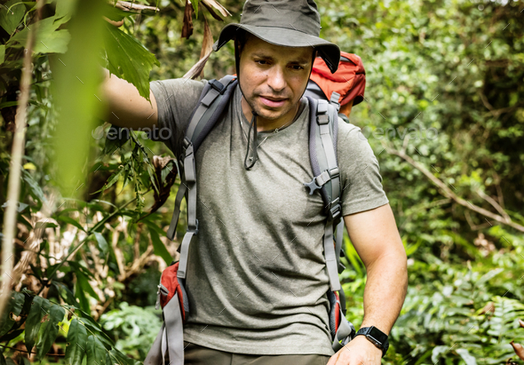 Male backpacker trekking in the forest - Stock Photo - Images