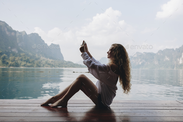 Woman using her phone by a lake - Stock Photo - Images