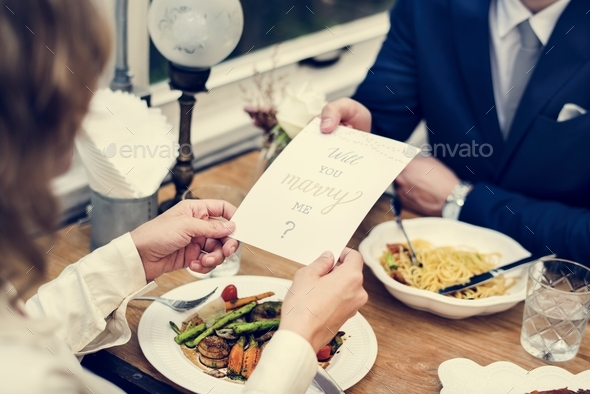 Man proposing girlfriend with card - Stock Photo - Images