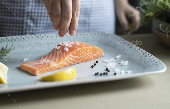 A person seasoning a fillet of salmon food photography recipe idea - Stock Photo - Images