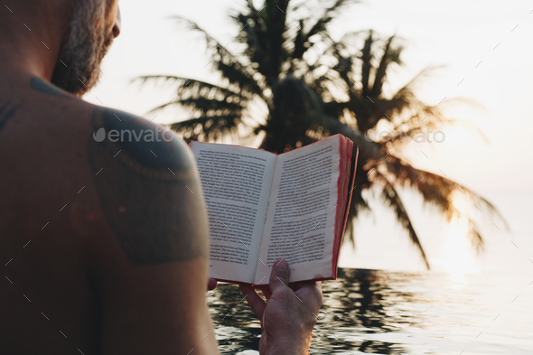 Man reading a book in the swimming pool - Stock Photo - Images