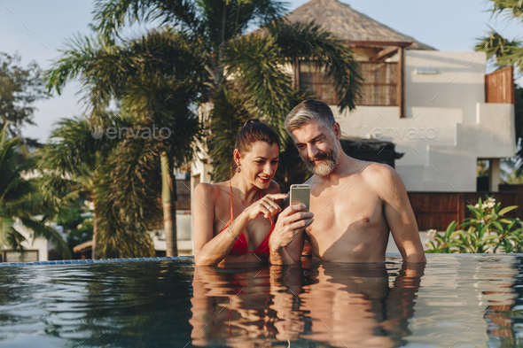 Honeymoon couple happy time in swimming pool - Stock Photo - Images