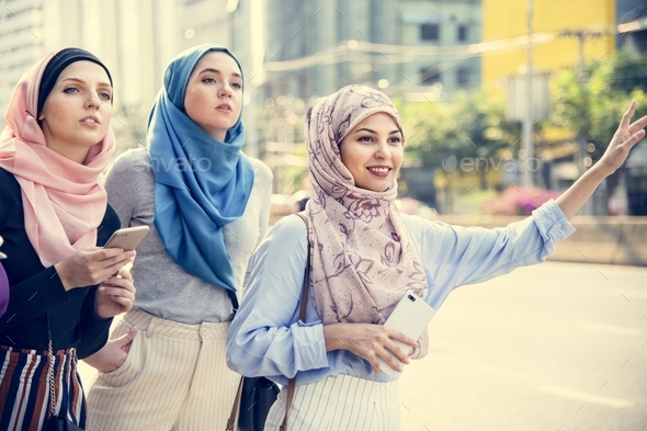 Islamic friends calling taxi on the street - Stock Photo - Images
