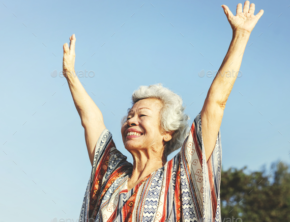Senior asaian woman raising her arms - Stock Photo - Images