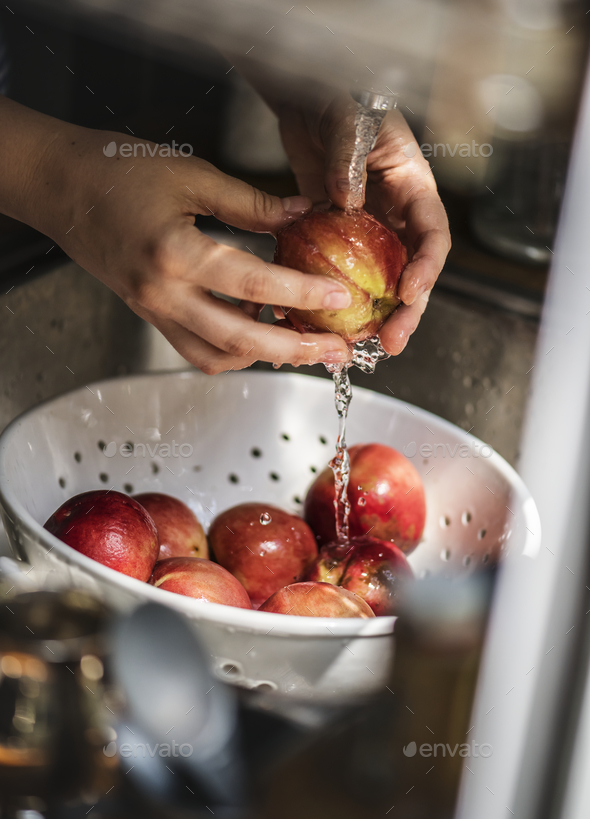 A person washing pomegranate under running water food photography idea - Stock Photo - Images