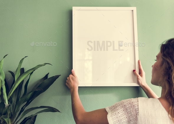Girl hanging a frame on a green wall - Stock Photo - Images