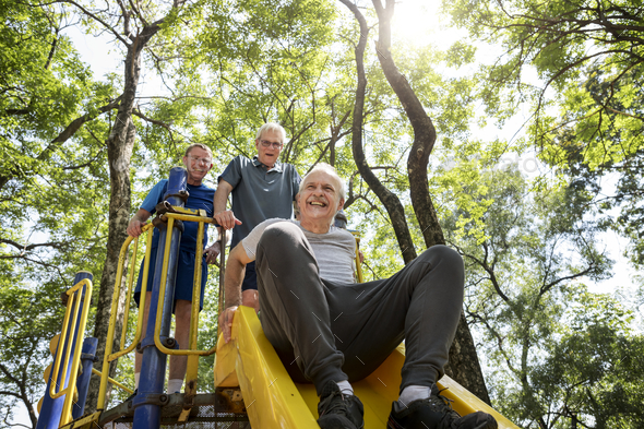 Senior men playing at a playground slide - Stock Photo - Images