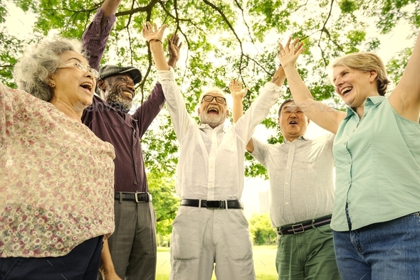 Group of happy retired senior friends  in the park cheering - Stock Photo - Images
