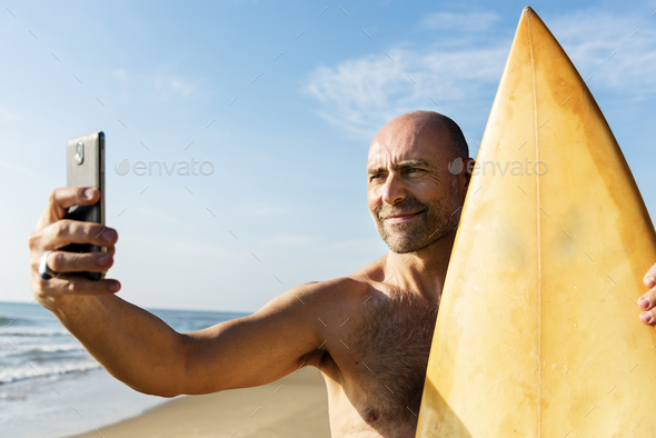 Man holding surfboard taking selfie - Stock Photo - Images