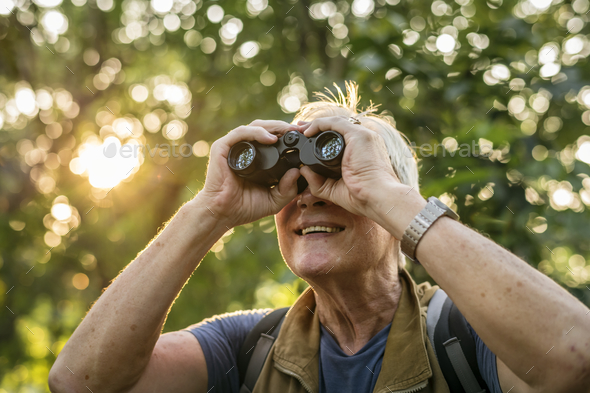 Elderly man watching birds with binoculars - Stock Photo - Images