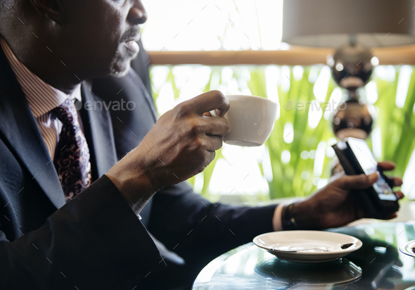 Businessman in cafe for a hot drink - Stock Photo - Images