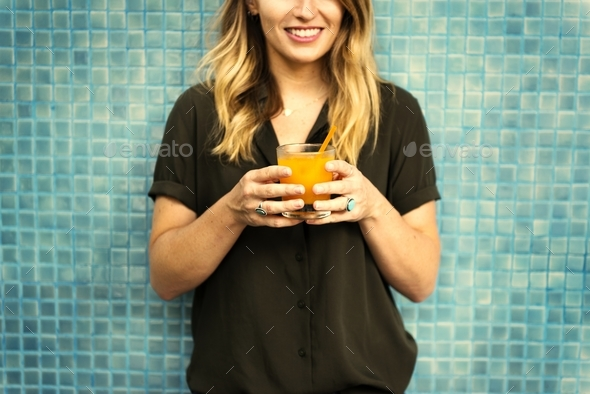 Woman holding a glass of orange juice - Stock Photo - Images