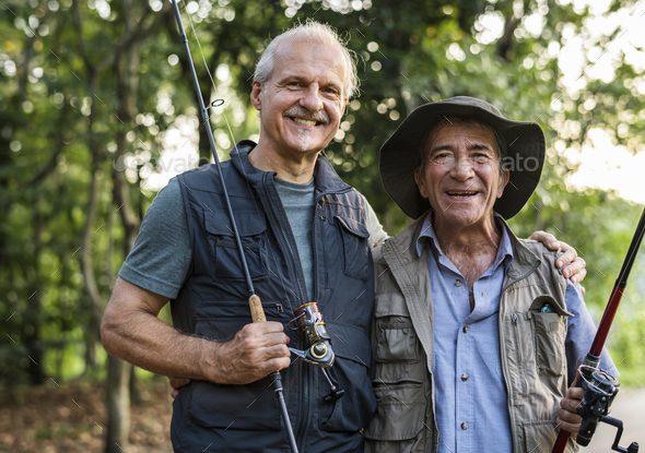 Senior friends fishing by the lake - Stock Photo - Images