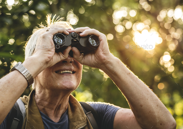 Mature man watching birds through binoculars - Stock Photo - Images