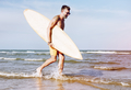 Mature man carrying a surfboard - PhotoDune Item for Sale