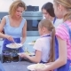 Woman in the Kitchen Treats Children or Adolescents To Pasta with Sour Cream Sauce - VideoHive Item for Sale