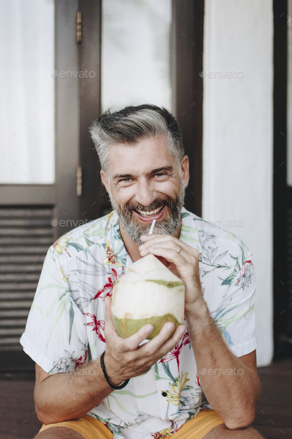 Man drinking a fresh coconut - Stock Photo - Images