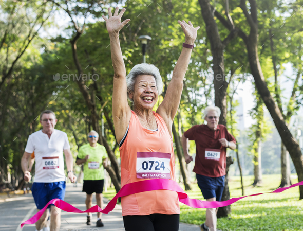 Happy senior running through the finish line - Stock Photo - Images