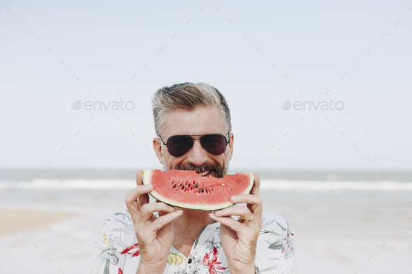 Mature man eating watermelon at the beach - Stock Photo - Images