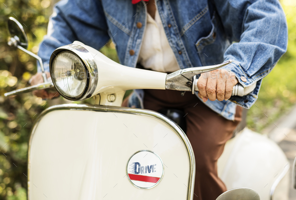 Closeup of a woman riding a classic scooter - Stock Photo - Images