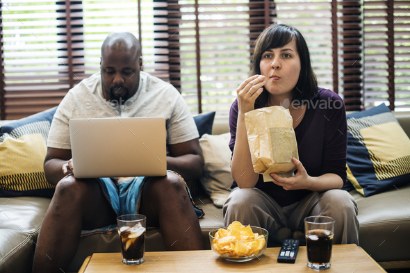 Couple watching tv on the sofa - Stock Photo - Images