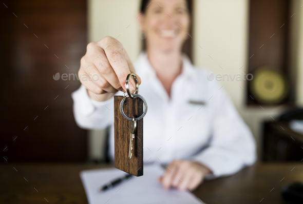 Receptionist handing room key to guest - Stock Photo - Images