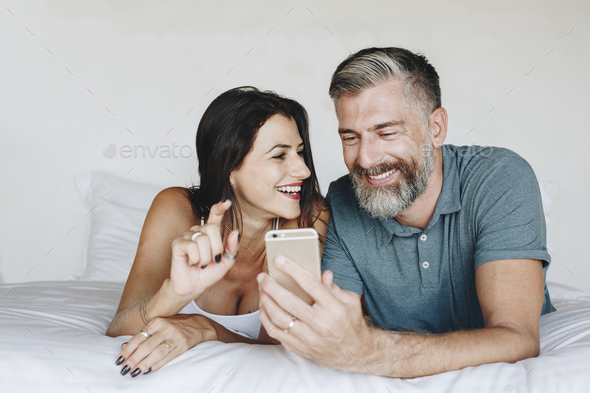 Couple using a smartphone in bed - Stock Photo - Images