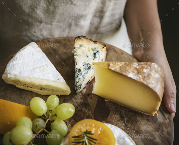 Person holding a platter of green grapes and different types of cheese - Stock Photo - Images