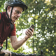 Senior cyclist using the gps on his phone - PhotoDune Item for Sale