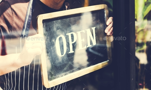 Man putting on shop open sign - Stock Photo - Images