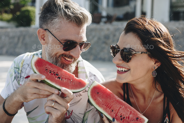 Couple eating watermelon at the beach - Stock Photo - Images