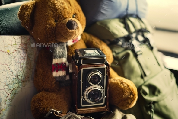 Closeup of brown bear doll with camera and map traveling - Stock Photo - Images